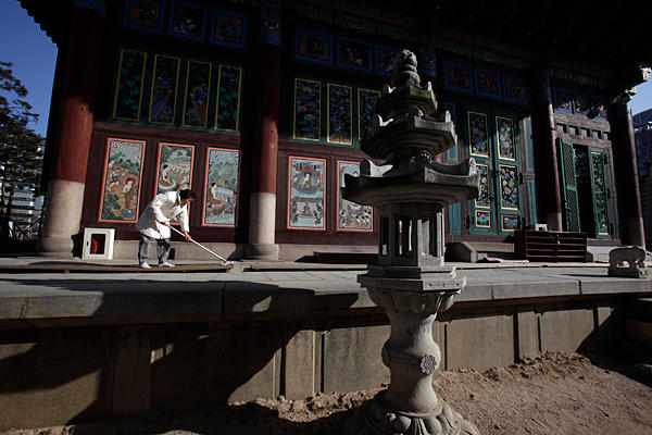 A South Korean woman cleans the walkway outside a Buddhist temple in Seoul